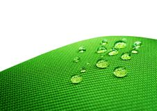 Green waterproof fabric with waterdrops close up on white. Background stock images