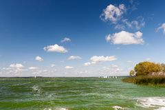 Green waters under blue sky with clouds Stock Photography