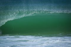 A green wave breaks on the shoreline. Water spray Royalty Free Stock Image