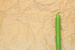 Green wax crayon on a recycled crumpled paper surface Stock Photography