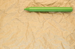 Green wax crayon on a recycled crumpled paper surface Royalty Free Stock Photo
