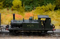 Green weathered steam engine with driver model train Royalty Free Stock Photo