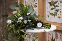 Green wedding bouquet. Of eucalyptus, ivy, fern, aspidistra, ruskus, date fruit, pink, ranunkulyus with flax box, green and brown velvet ribbons on white stand Stock Images