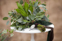 Green wedding bouquet. Of eucalyptus, ivy, fern, aspidistra, ruskus, date fruit, pink, ranunkulyus with flax box, green and brown velvet ribbons on white stand Royalty Free Stock Photo