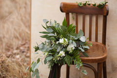 Green wedding bouquet. Of eucalyptus, ivy, fern, aspidistra, ruskus, date fruit, pink, ranunkulyus with flax box, green and brown velvet ribbons on white stand Stock Photos