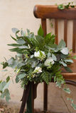 Green wedding bouquet. Of eucalyptus, ivy, fern, aspidistra, ruskus, date fruit, pink, ranunkulyus with flax box, green and brown velvet ribbons on white stand Royalty Free Stock Photography