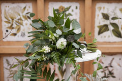 Green wedding bouquet. Of eucalyptus, ivy, fern, aspidistra, ruskus, date fruit, pink, ranunkulyus with flax box, green and brown velvet ribbons on white stand Royalty Free Stock Images