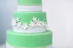 Green wedding cake decorated with white flowers Stock Image