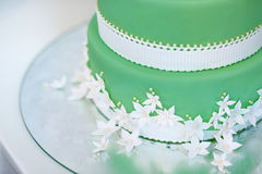Green wedding cake decorated with white flowers Royalty Free Stock Photography