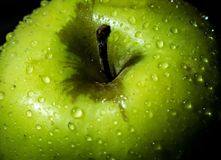Green wet apple with drops closeup royalty free stock photo