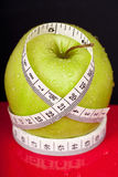 Green and wet apple with measure tape Royalty Free Stock Photo