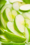 Green wet apple slices. Food background Stock Image