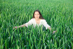 Green wheat field. Beautiful girl emerges from a wheat field (spring background Stock Photo