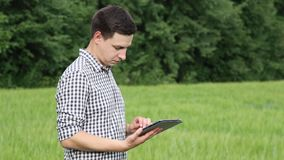 The caucasian male brunette farmer on the field works with a tablet. Scientist working in the field with agricultural stock video footage