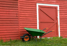 Green wheelbarrow, red barn Royalty Free Stock Image