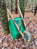 Green wheelbarrow in the woods. A green wheelbarrow in the woods propped against a tree, surrounded by leaves, concept for fall yard work royalty free stock photos