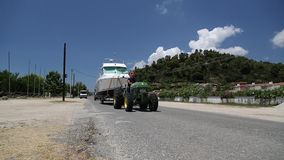 Green wheeled tractor transporting the boat on a paved road stock footage