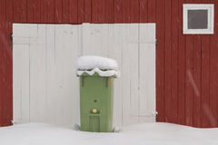 Green wheeled trash can. Red swedish barn in snow with a wheeled trash can while snowing Stock Photo