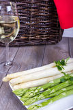 Green and white asparagus and wine in front of a basket Royalty Free Stock Image