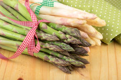 Green and white asparagus on wooden table in closeup. Stock Photography