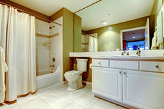 Green and white bathroom with sink and tub with curtain. White tile floor Royalty Free Stock Photo