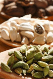 Green white and black cardamom seeds on wood Royalty Free Stock Photography