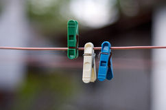 Green, white, blue clothes peg on a washing line. Closeup of Colorful clothes peg on a rope isolated on light blurred background rr royalty free stock photos