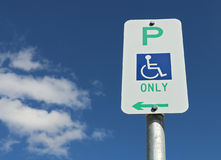 Green white and blue Wheelchair Only Parking sign in a cloudy blue sky Royalty Free Stock Photography