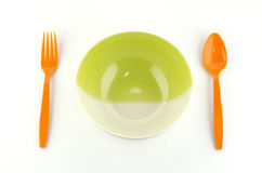 Green white bowl with orange spoon and fork on white ba Stock Images