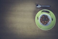 Green and White Ceramic Plate Beside Stainless Steel Spoon on Brown Table Royalty Free Stock Image