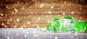 Green and white christmas gifts and baubles on snow 3D rendering. Green and white christmas gifts and baubles on snowy background 3D rendering royalty free illustration