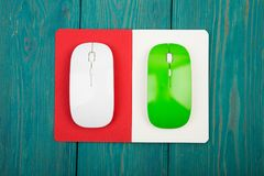 Green and white computer mouses, notepad on blue wooden desk. Green and white computer mouses, notepad on blue wooden background stock photography