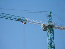 Green and white construction hoisting crane over c Royalty Free Stock Image