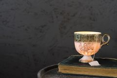 Green white cup of tea on vintage book, against dark background. Copy space stock photos