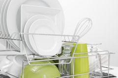 Green and white dishes drying on dish rack Royalty Free Stock Photos
