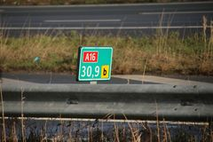 Green and white distance sign in kilometers at a shoulder along motorway A16 at Zwijndrecht in the Netherlands. Green and white distance sign in kilometers at a royalty free stock photography