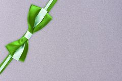 Green and white gift ribbon and knot on a silver textured pattern background. royalty free stock image