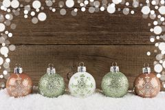 Green, white & gold Christmas ornaments in snow Stock Images