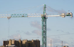 Green and white hoisting crane on construction Royalty Free Stock Photo