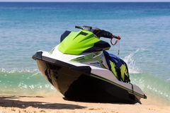 A green-white jet ski is on a beach in waves of blue sea in the sunny weather. Active rest is happy time for all family. royalty free stock photo