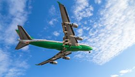 A green and white 747 landing at Vancouver International Airport on a sunny day. royalty free stock images