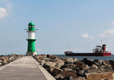 Green and white lighthouse and cargo ship leaving port Royalty Free Stock Photos
