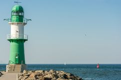 Green white lighthouse at the harbor entrance in Warnemünde stock photography