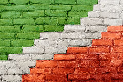 Green, white and red painted brick wall resembling Italian flag. Diagonal stripes, close up view Stock Photo