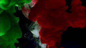 Green, white and red watercolor ink in water. A powerful explosion of colors.