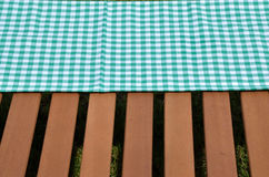 Green and white tablecloth and wooden surface Stock Photography