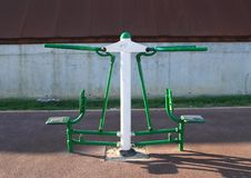 Green and white training machine for bodybuilding. Green and white training and exercise machine for bodybuilding on pedestrian walk royalty free stock photography