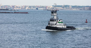 Green and White Tug Boat in New York Harbor Stock Images
