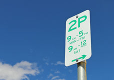 Green and white Two Hour Parking sign in a blue sky Stock Images