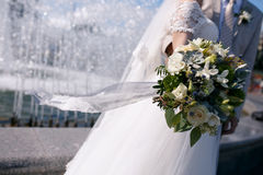 Green and white wedding bouquet in hands of the bride with a fluttering in the wind blue lace ribbon. On a background of a fountain Stock Image